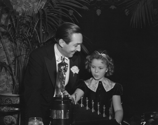 "Walt Disney in 1939 receiving one Oscar statuette and seven miniature statuettes from Shirley Temple for ""Snow White and the Seven Dwarfs"""